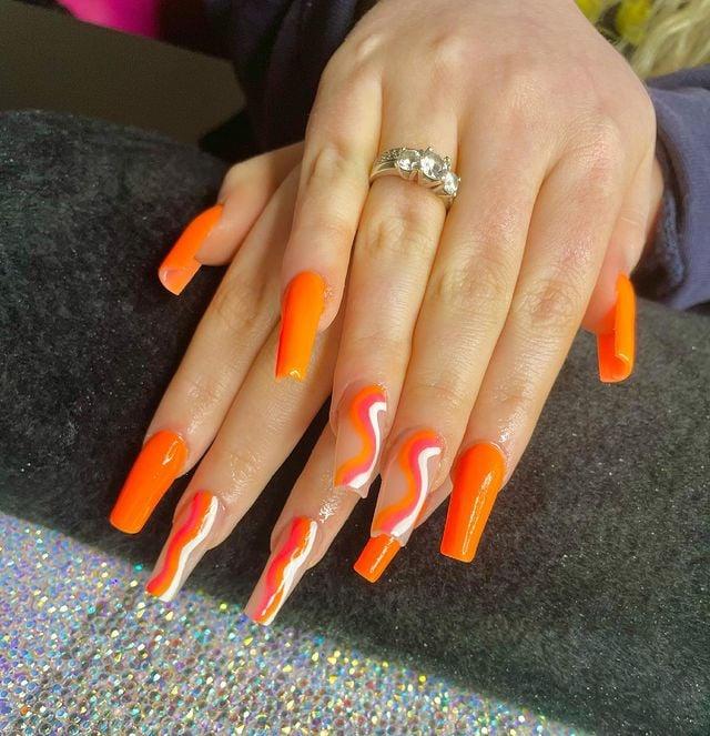 Chica con unas uñas extra largas con diseño en color naranja