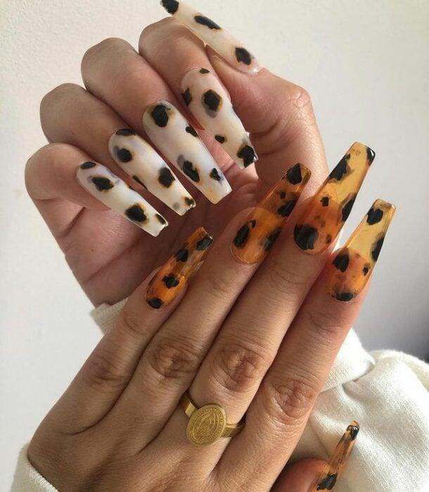 Chica con unas uñas extra largas con diseño en color amarillo con blanco