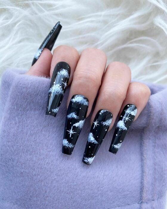 Chica con unas uñas extra largas con diseño en color negro con nubes