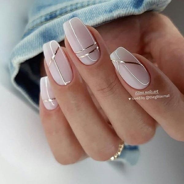 Chica con las uñas pintadas en color rosa con un toque de plateado