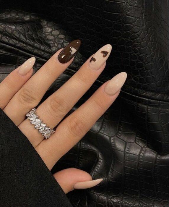 Chica con las uñas pintadas en diferentes tonos de café con nude
