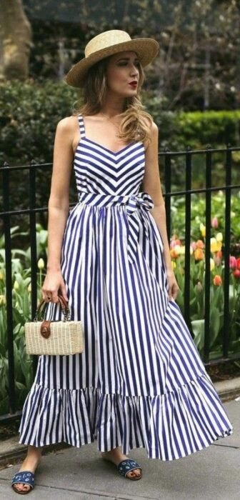 Chica usando un vestido azul de líneas con sandalias