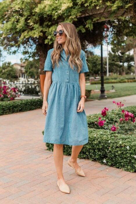 Chica usando un vestido de mezclilla con flats