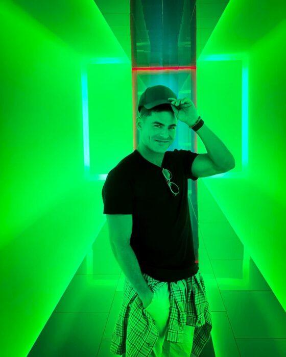 Zac Efron posando para una fotografía mientras está en un cuarto verde