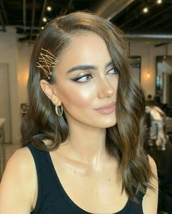 chica con cabello en ondas y clips a un costado ;13 Peinados para enchularte en menos de 15 minutos