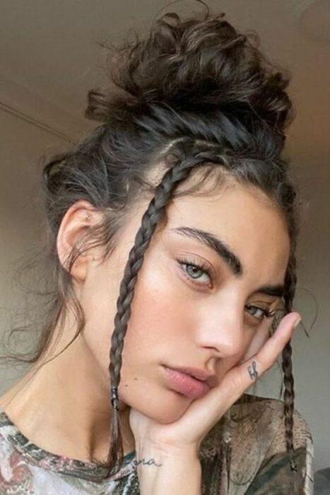 chica con bun alto y trenzas en fleco ;13 Peinados para enchularte en menos de 15 minutos