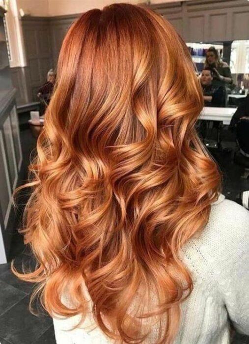 Chica con cabello largo mostrando su tinte ;13 Pruebas de que el tinte 'sunset copper' es la nueva tendencia