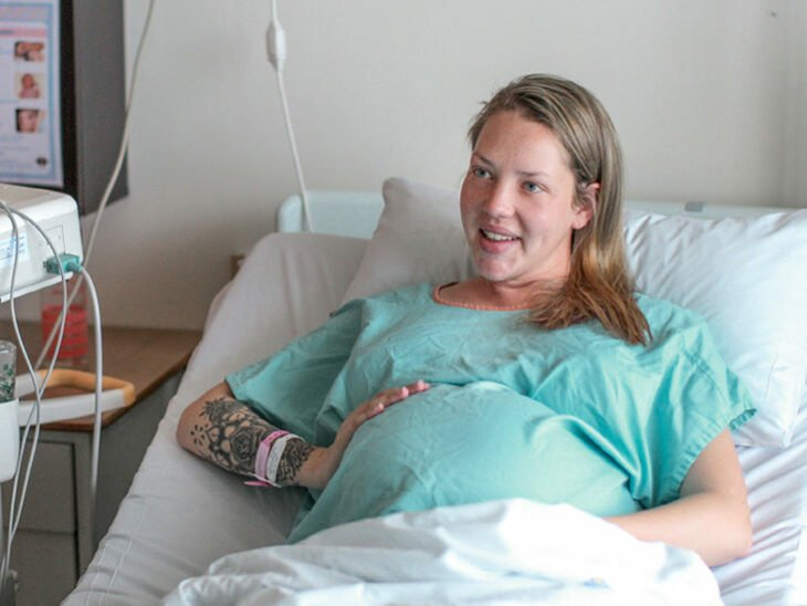 Mujer embarazada sentada en una cama de hospital
