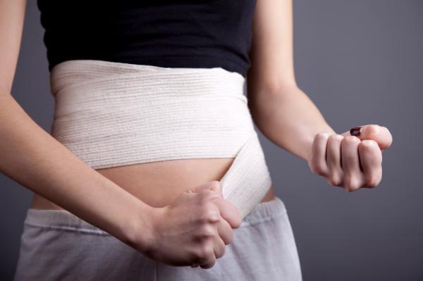 Mujer poniéndose un vendaje abdominal