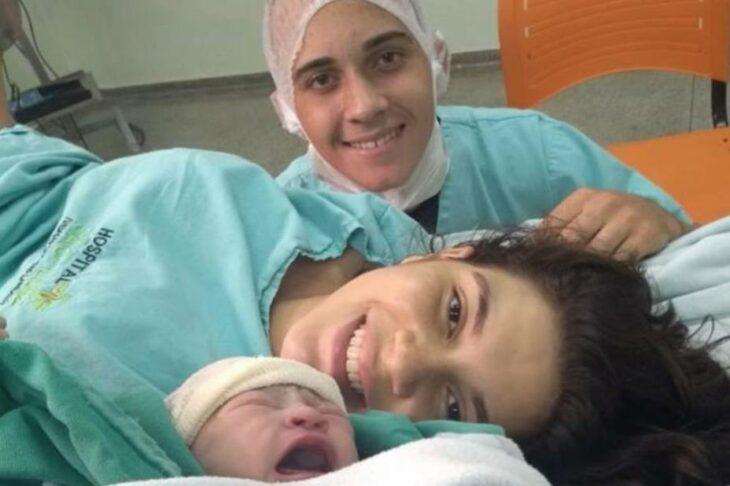 Chica viendo a su bebé recién nacido