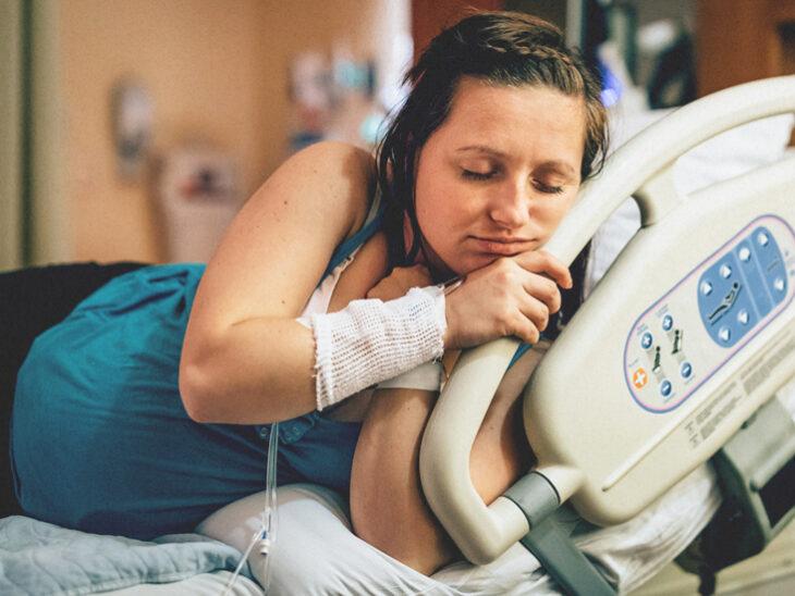 Mujer embarazada sujetando la cama del hospital