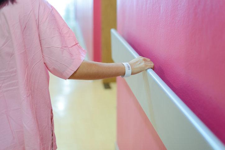Mujer caminando mientras se sujeta de una pared en el hospital