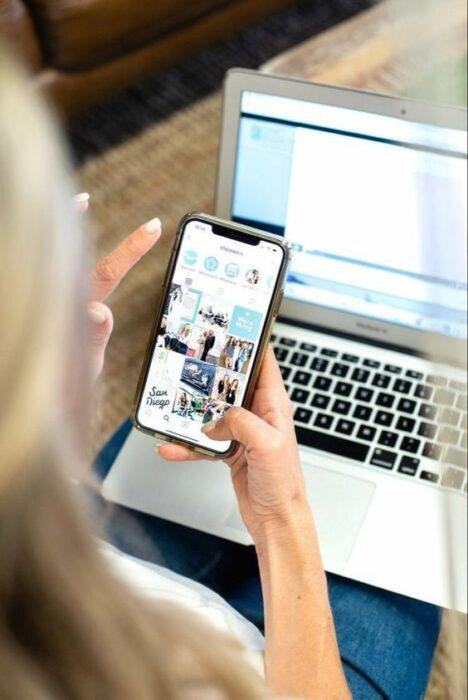 Mujer revisando su celular y su computadora
