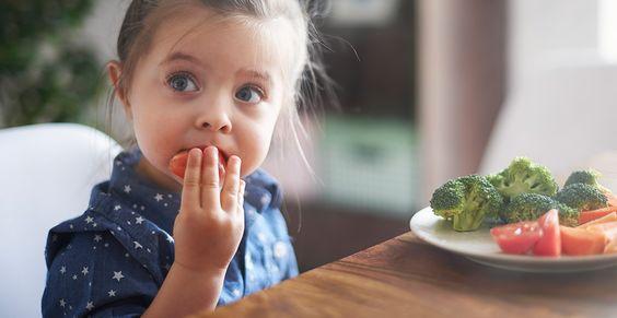 Niña comiendo un platillo con verduras