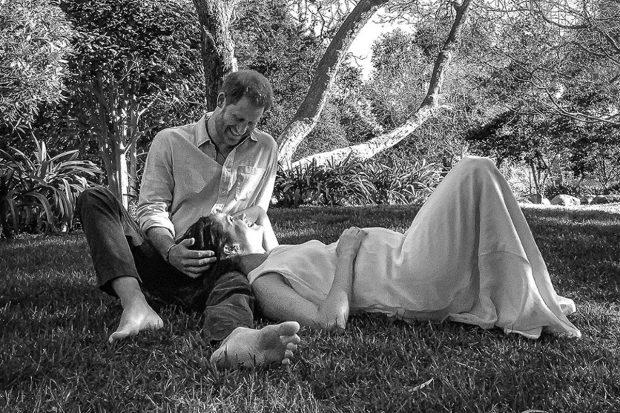 Meghan Markle y el príncipe Harry sentados bajo un árbol