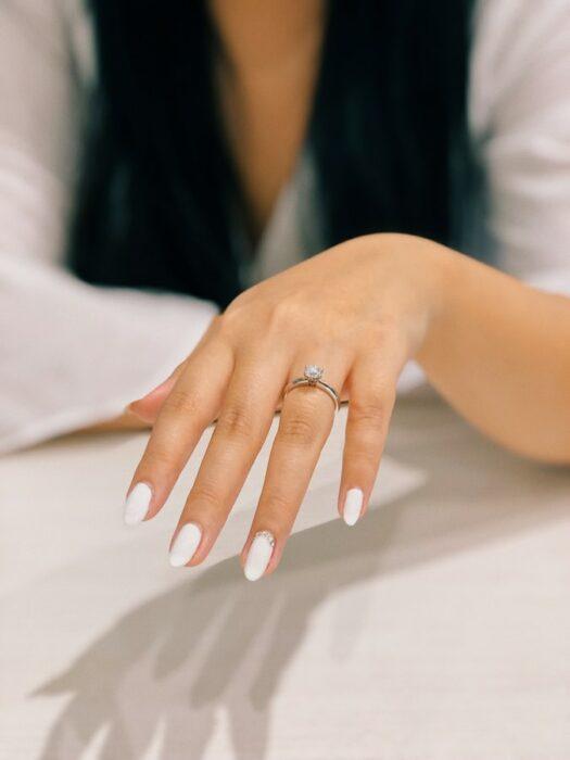 Chica mostrando su anillo de compromiso; Entre más caro sea el anillo de compromiso más rápido llegará el divorcio estudio