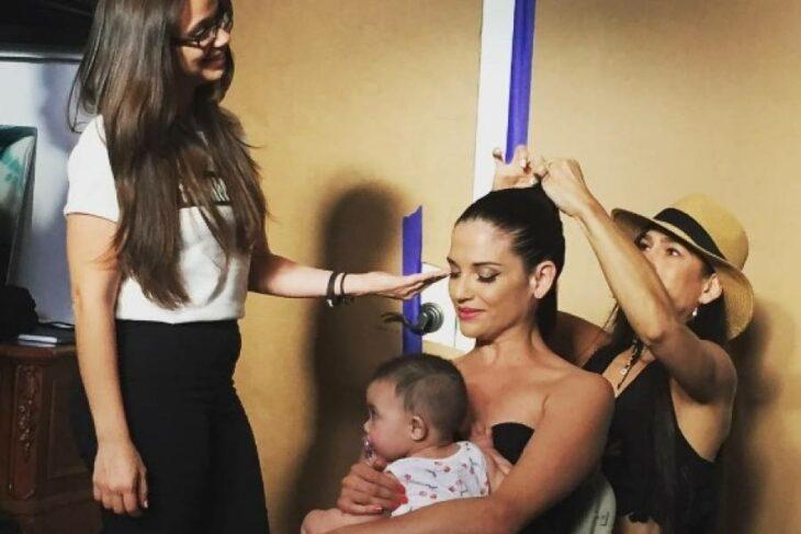 Natalia Jiménez sosteniendo a su bebé mientras la maquillan