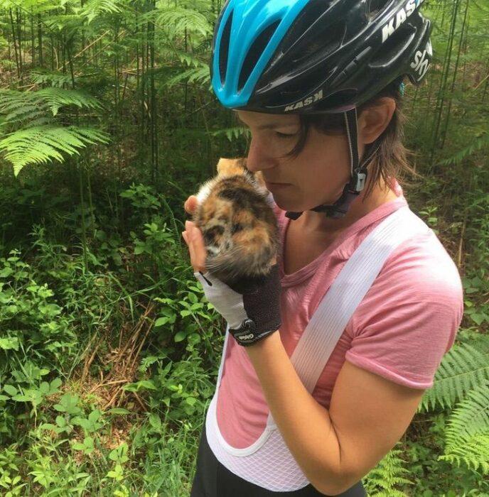 Mujer rescatando a una gatita que estaba perdida en el bosque