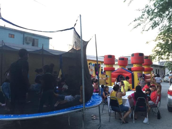 Personas en una fiesta infantil con inflables y mesas
