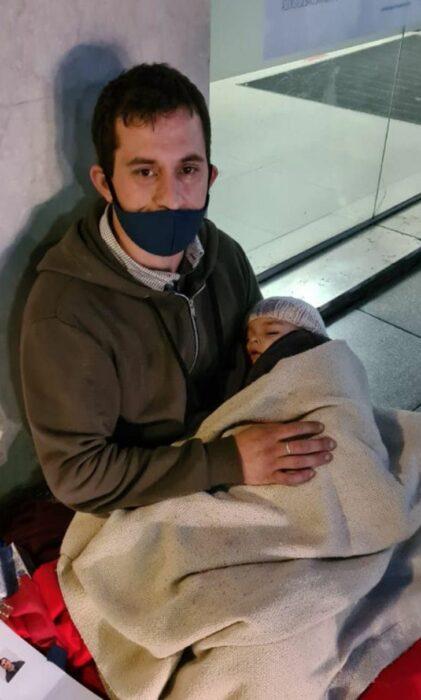 Hombre abrazando a su bebé mientras piden dinero afuera de un banco