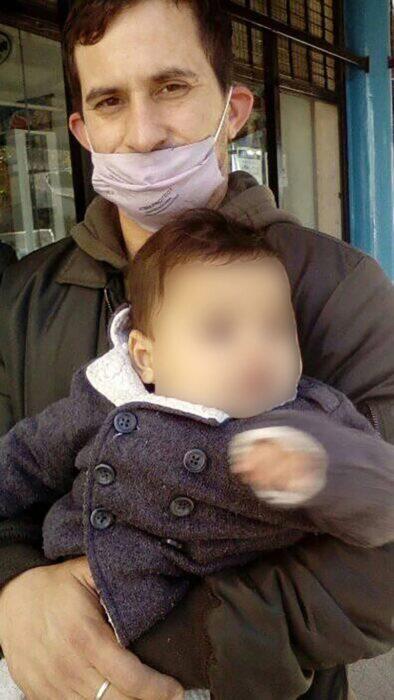Hombre sosteniendo a su bebé en brazos mientras sonríe