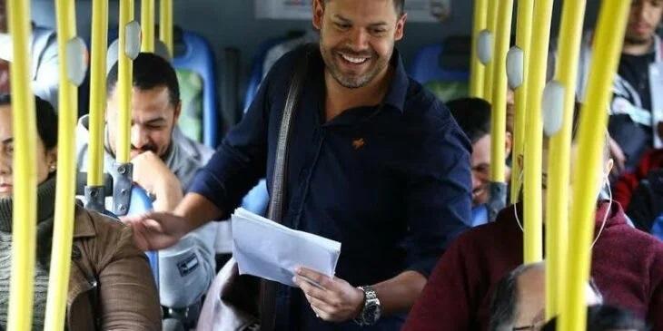 Hombre en el transporte publico recogiendo currículos
