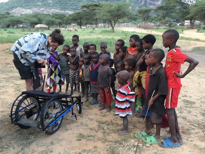 Joven enseñando cómo funciona su silla de ruedas hecha con materiales reciclados