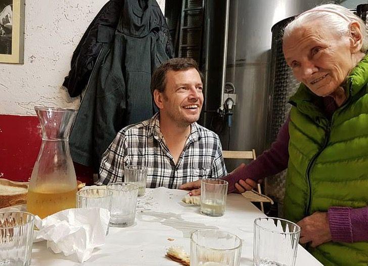 Hombre y su madre con alzheimer sentados en la cocina disfrutando de la comida