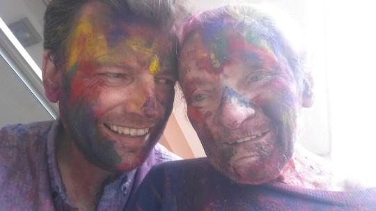 Hombre junto a su madre llenos de polvos de colores
