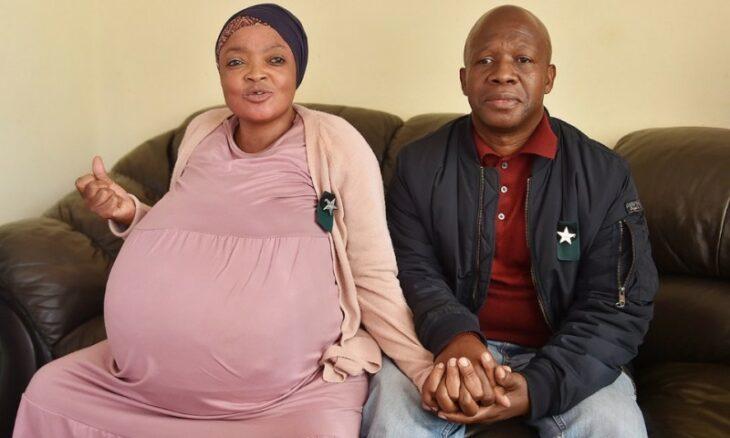 Mujer sudafricana con un enorme vientre de embarazo sentada junto a su pareja
