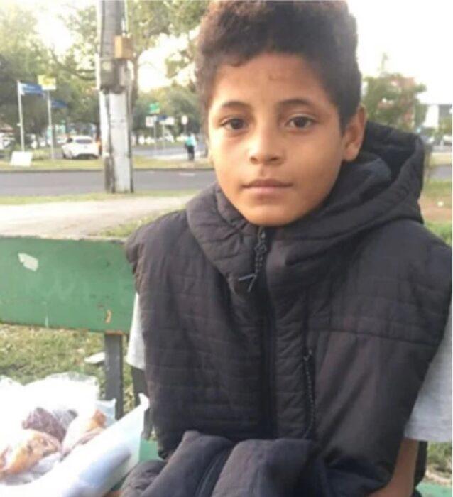 Niño sentado en la banca de un parque vendiendo pasteles