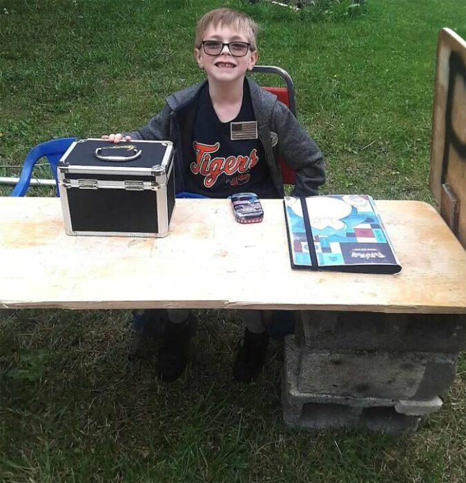 Chico con una mesa afuera de su casa vendiendo productos de pokémon