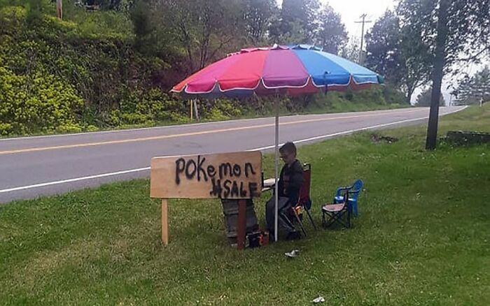 Niño sentado afuera de su casa en una venta de garage