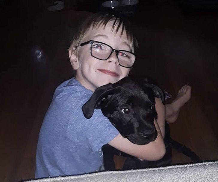 Niño jugando con su cachorro labrador de color negro