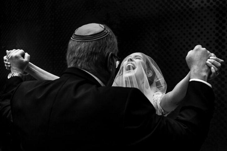 Padre e hija sonriendo el día de la boda mientras se ven por primera vez