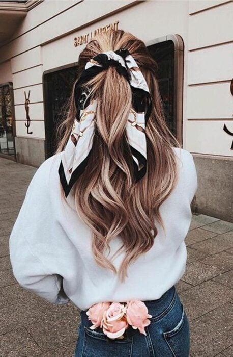 Chica usando un pañuelo en la cabeza para peinarse