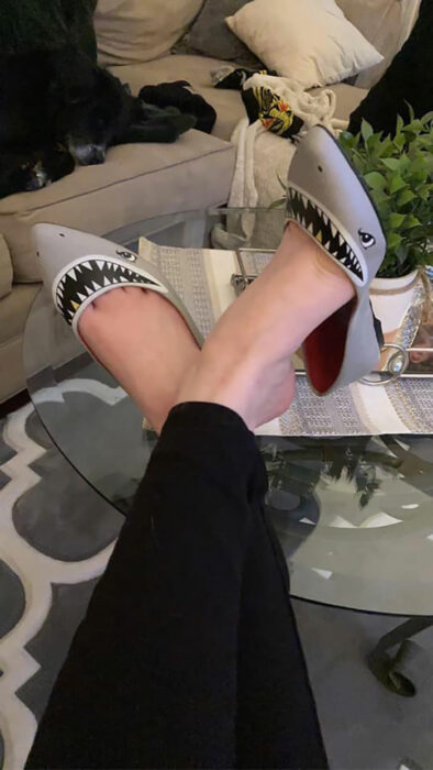 Chica usando unos zapatos de tiburón