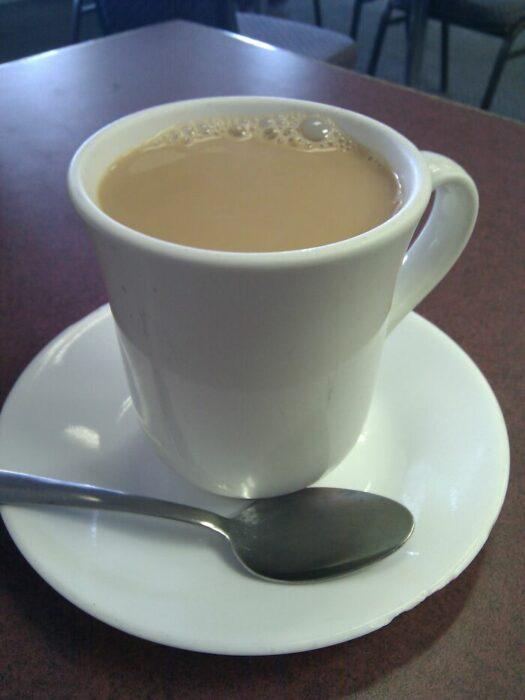 Taza de color blanco con café con leche
