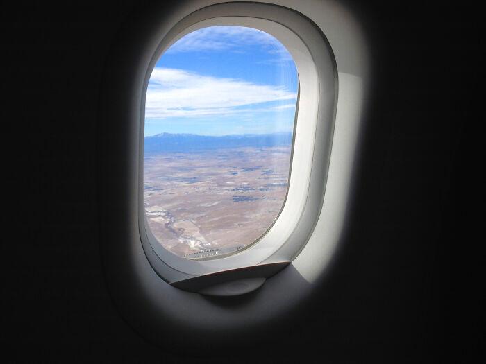 Ventanilla de avión con un paisaje que se ve desde el cielo