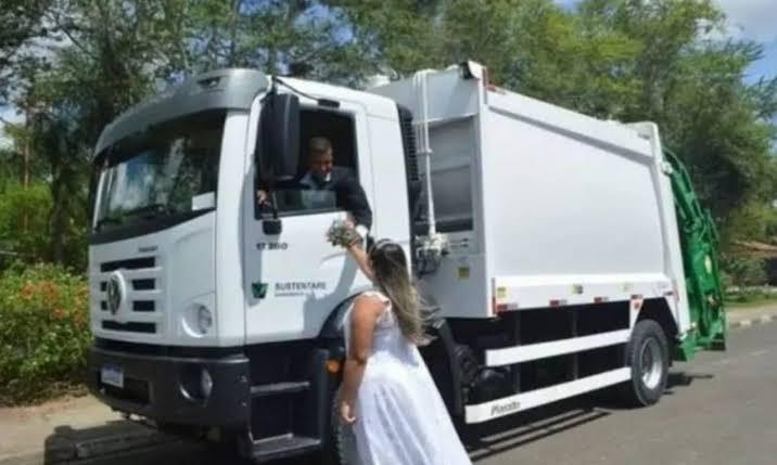 Pareja de novios tomados de la mano frente a un camión de basura; Recién casados toman sus fotos de boda en un camión de basura; él es recolector
