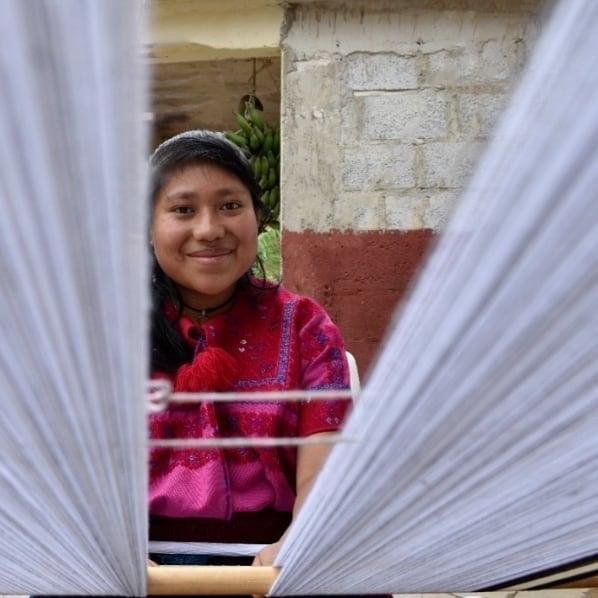 Mujer indigena mexicana tejiendo en un telar de algodón