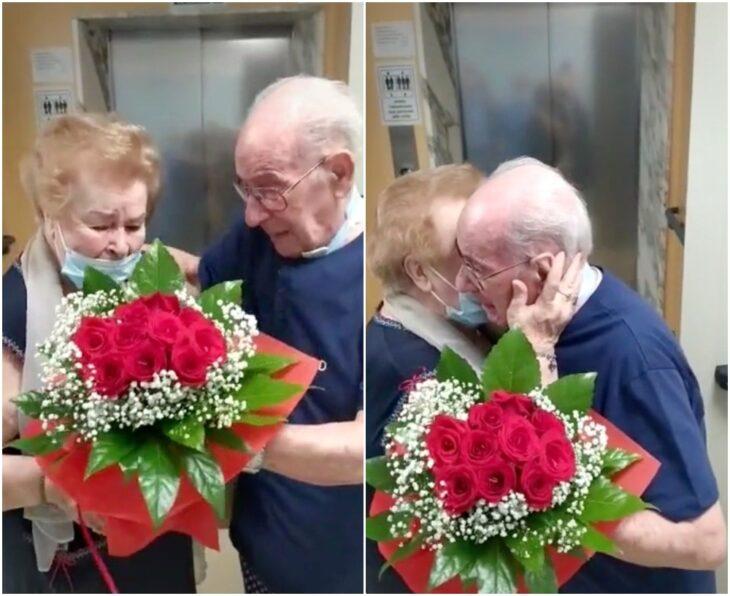 Abuelitos abrazados y sosteniendo un ramo de rosas