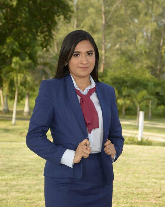 Evelin Hipólito con traje sastre en su graduación ;Chica posa orgullosa con su título universitario en el banco donde vendía dulces