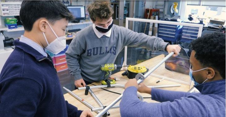 Estudiantes creando un soporte en un laboratorio