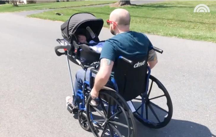 Hombre en silla de ruedas paseando a su bebé en un portabebé