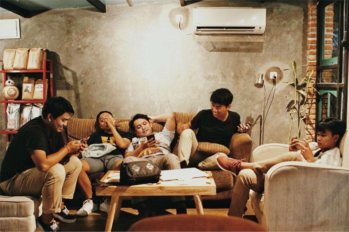 Amigos sentados en un sofá conversando y viendo sus celulares