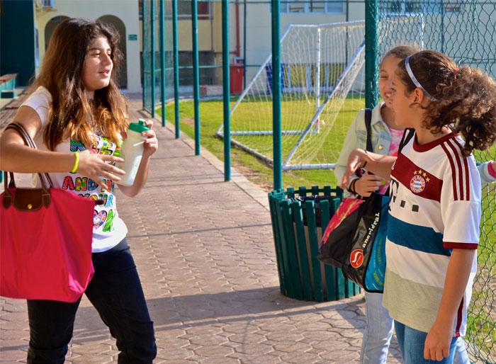 Chicas conversando mientras están afuera de una escuela