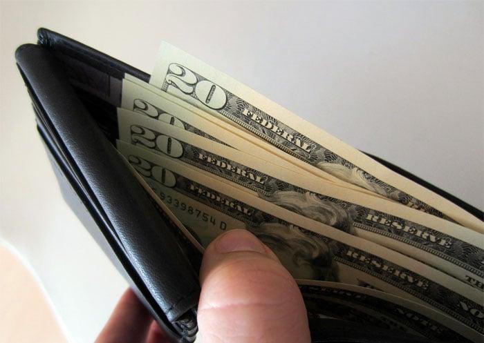 Chica sosteniendo una cartera con dinero