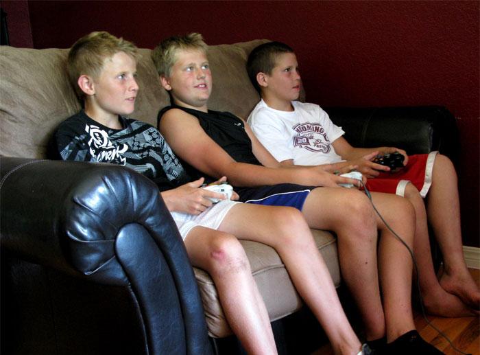 Niños sentados en una sala jugando Xbox
