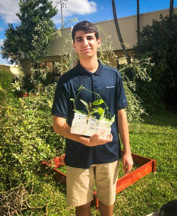 Ducan sosteniendo una maceta con flores ;Joven siembra miles de flores durante 12 años y logra salvar a cientos de mariposas en extinción